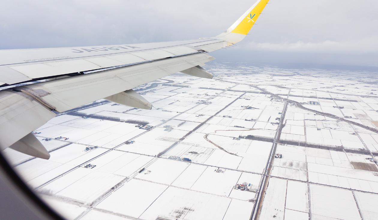 【写真でわくわく冬のバニラエア上空】(10:05)雲の下に降りて低空飛行。目の前に雪の畑が広がる。もうすぐ新千歳空港かな。
